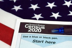 united-states-2020-census-packet-on-american-flag-with-blue-pen
